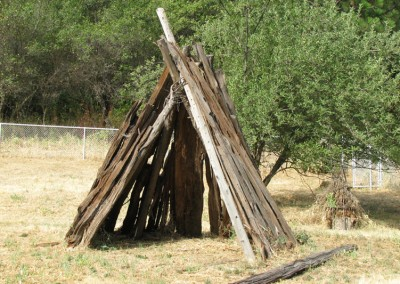 Umacha (house) Built with cedar poles for stability. Wrapped with grape vines to hold it together and covered with cedar bark. Pine needles were laid on the floor for comfort, and a fire pit in the middle for warmth.